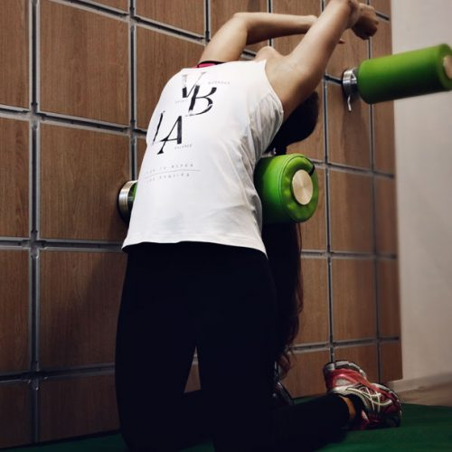 Stretching - Frau an einer Stretchwand